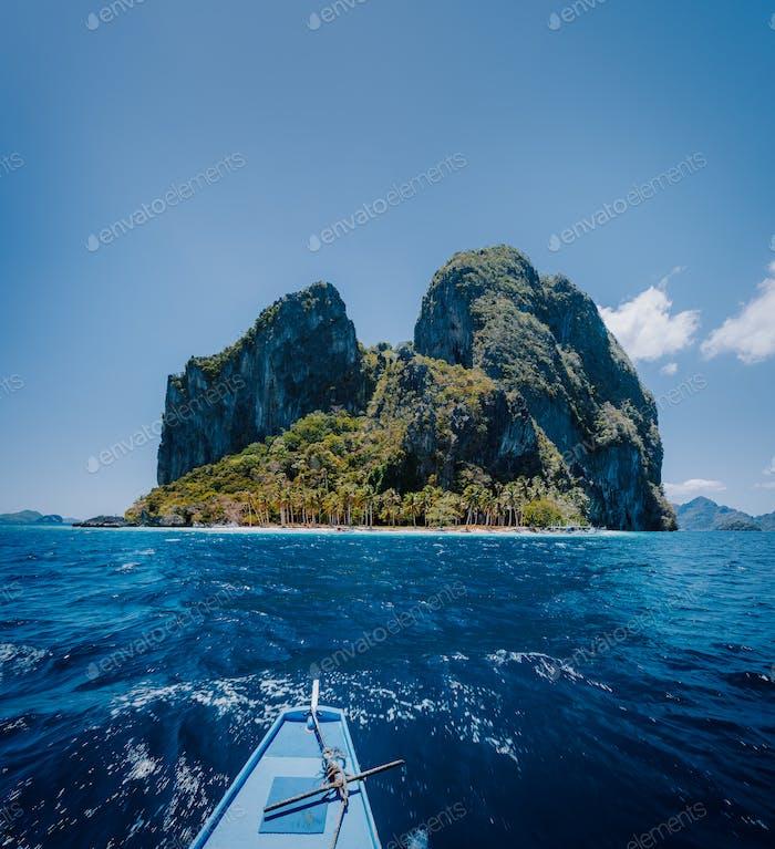 Philippino local boat facing impressive tropical Pinagbuyutan Island. El Nido, Palawan, Philippines