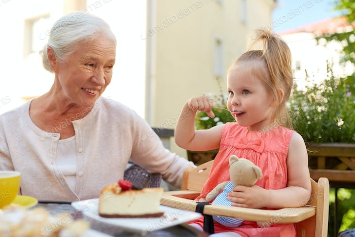 little girl with grandmother eating cafe