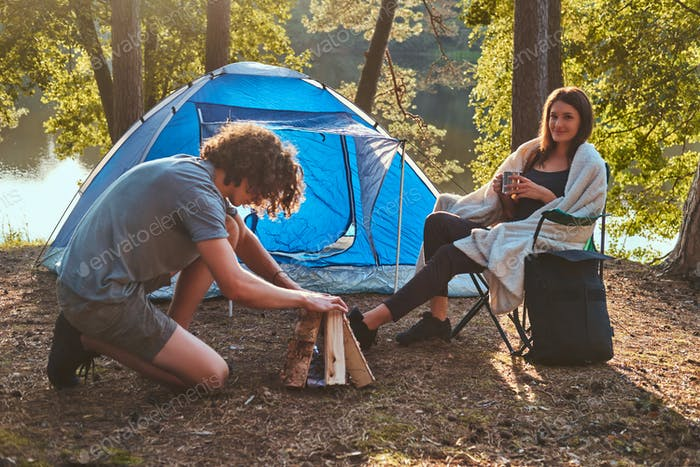 Young hiker couple at camp in the forest. Young guy tries to light a fire.
