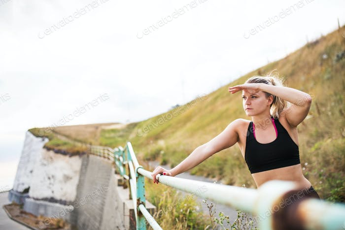 Young sporty woman runner in black activewear standing outside in nature, resting.