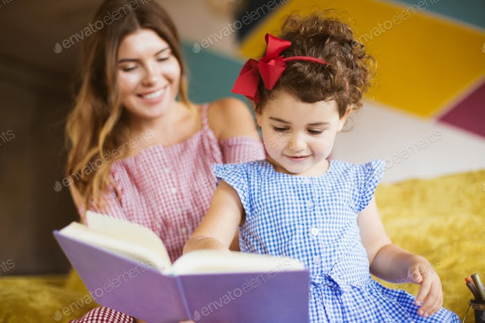 Pretty little girl with dark curly hair in dress happily reading