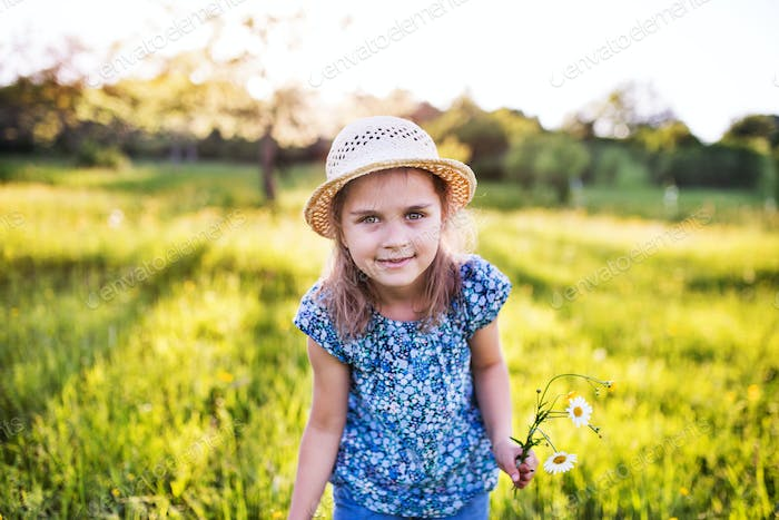 A portrait of a small girl in the garden in spring nature.