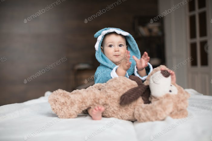 Happy baby boy in blue robe playing with teddy bear on bed