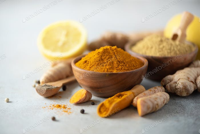 Ingredients for hot ayurvedic drink. Turmeric powder, curcuma root, cinnamon, ginger, lemon over
