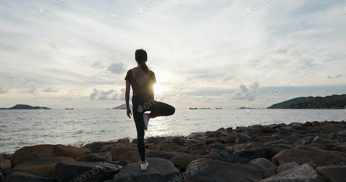Frau tun Yoga und sitzen am Meer