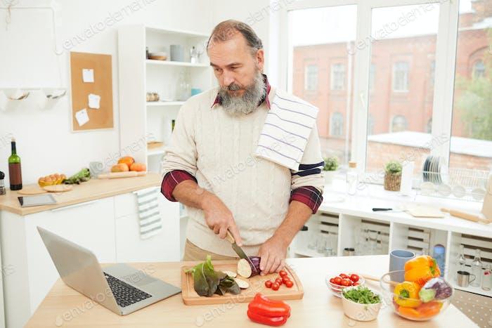 Senior Man Cooking by Online Tutorial