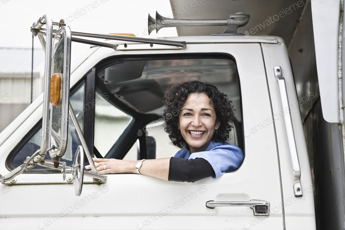 Hispanic woman truck driver and company delivery truck.
