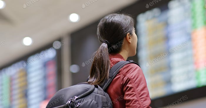 Young woman look at the flight number in the airport