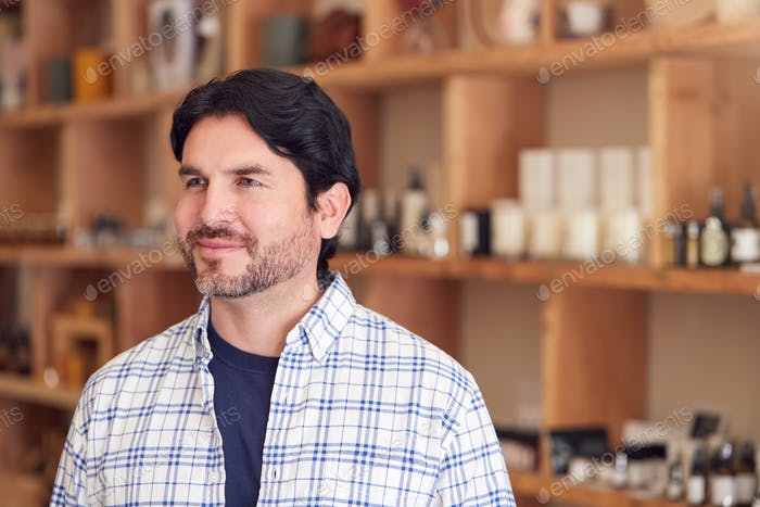 Male Owner Of Gift Store Standing In Front Of Shelves With Cosmetics And Candles