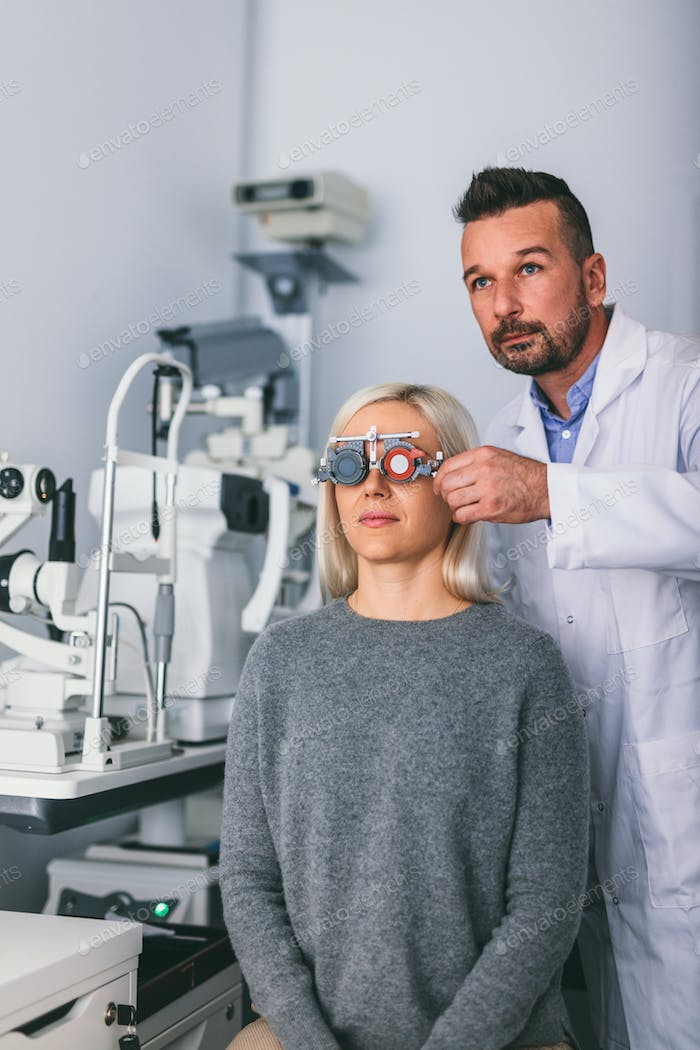Optician checking patient's eyesight with trial frame.