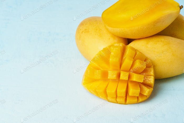 Four whole mango fruits on bright blue table and cut into slices. Large juicy yellow fruits
