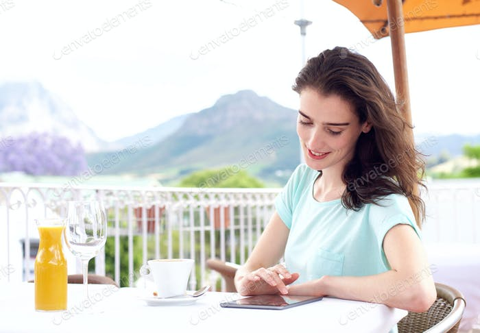 Smiling young woman sitting at outdoor cafe with digital tablet
