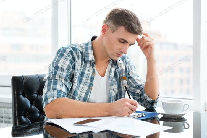 Handsome thoughtful man sitting and drawing in office
