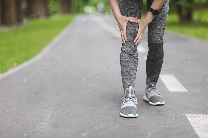 Knietrauma. Unrecognizable Frau Jogger Hütte Ihr Bein Während Laufen im Freien