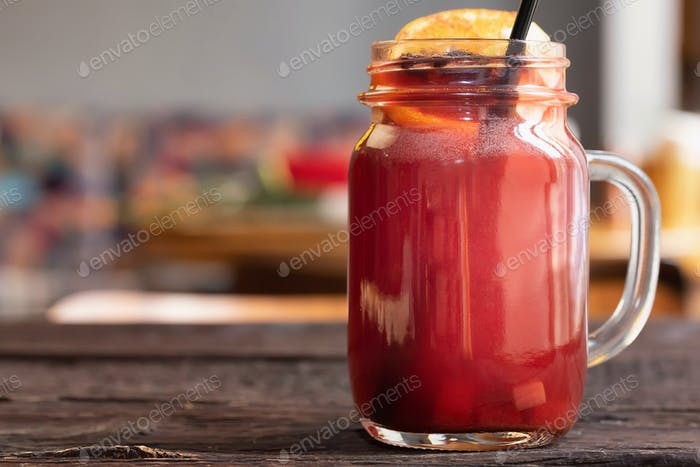 Close up glass jar with hot mulled wine and straw on dark wooden table