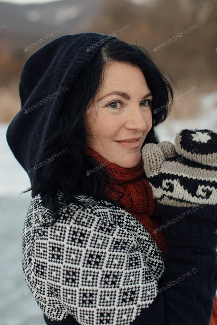 Portrait of a cheerful woman rubbing hands together to keep warm