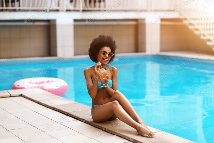 Pretty black lady in swimwear sipping her refreshing cocktail and relaxing by pool outside