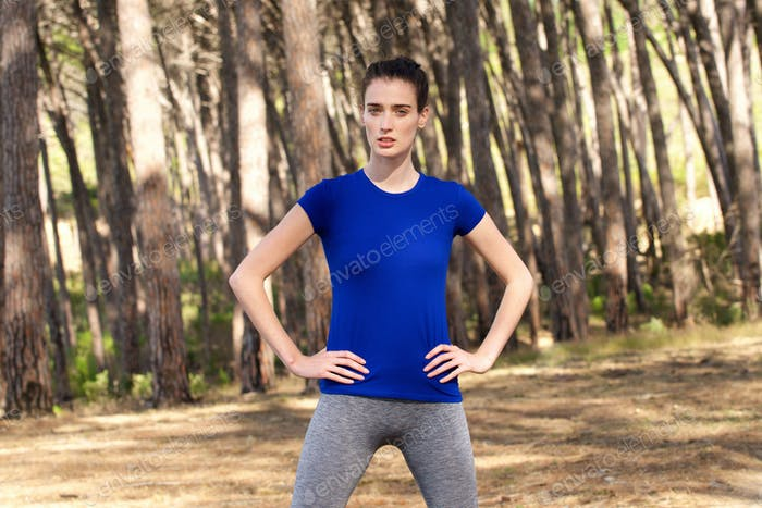 Sporty woman with both hands on hips standing in forest