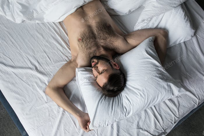 top view of handsome shirtless bearded man sleeping in bed under white blanket