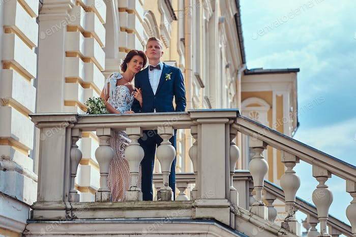 Portrait of happy newlyweds embracing while posing on the stairs of the beautiful old palace.