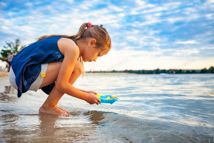 Caucasian girl playing with rubber duck toys on beach