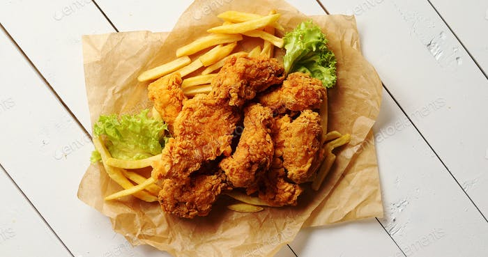Lettuce and French fries near chicken wings