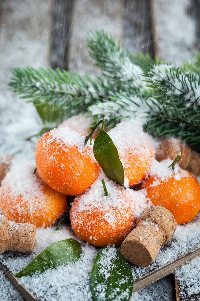Fresh tangerines with leaves on a snow