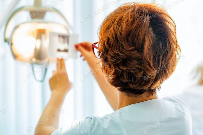 A dentist examines x ray in her hands