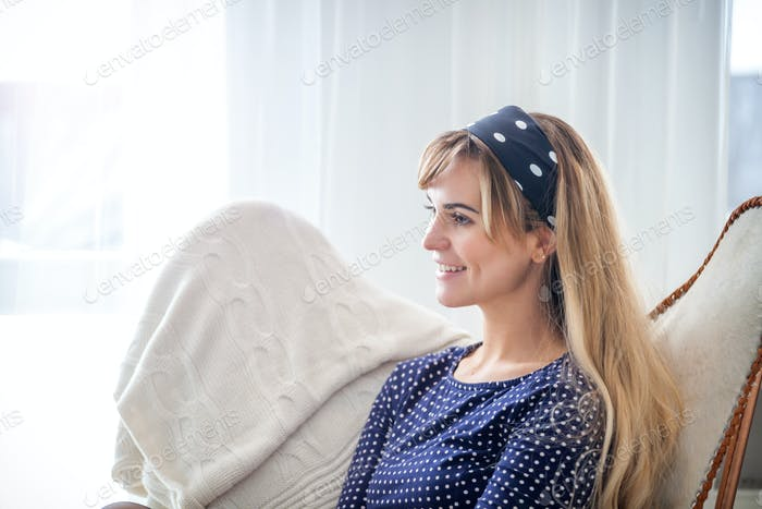 Cheerful smiling young woman sitting on armchair at home, positive emotions