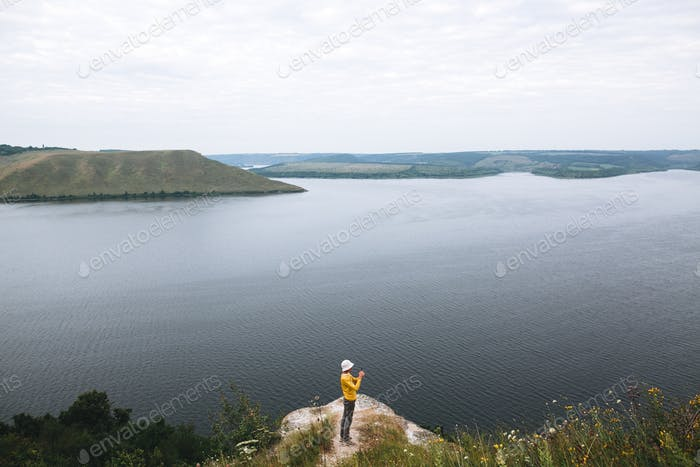 Hipster teenager standing on top of rock mountain and looking on river