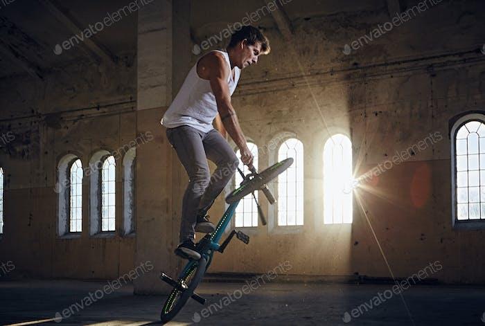 BMX Stunts in einer gotischen Halle mit Sonnenstrahlen.