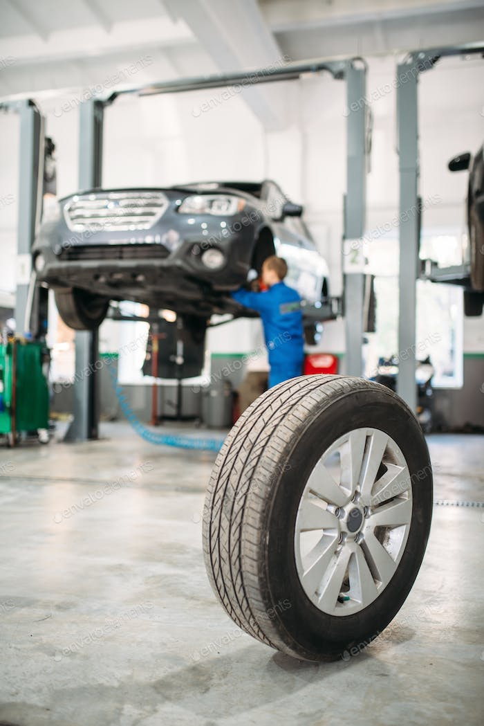 Wheel on the floor in tire service, car on lift