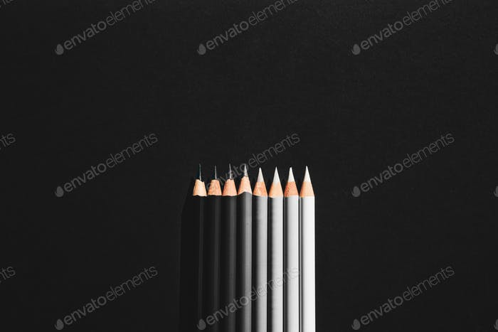 Pencil of shades of grey in black background.
