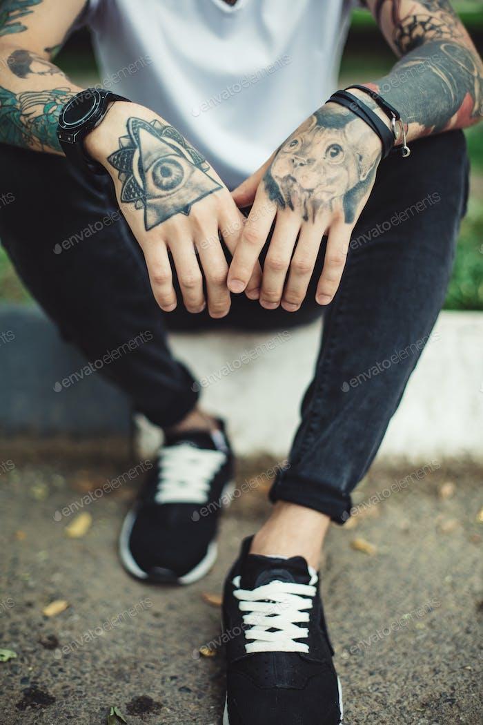Crop tattooed man outside