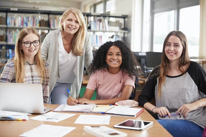 Woman Teacher Working With Female College Students In Library