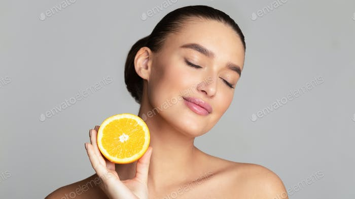 Beautiful pretty woman holding half of orange