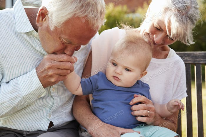 Grandparents Sitting On Seat In Garden With Baby Grandson