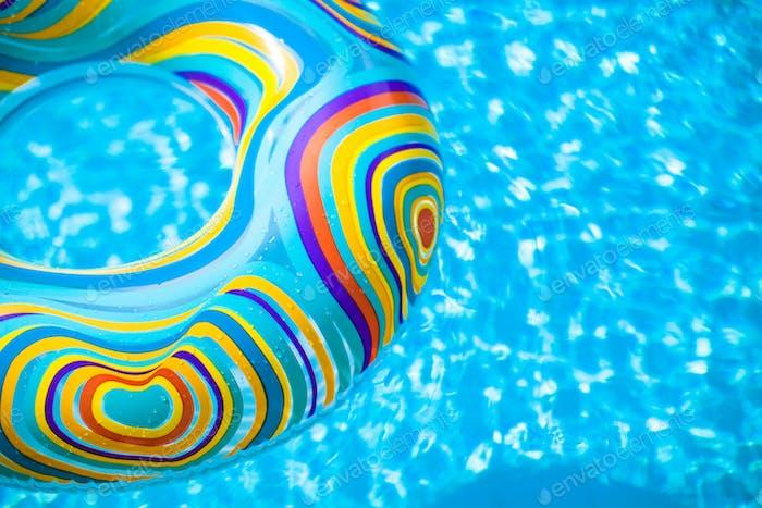 Aufblasbare bunten Gummiring schwimmend im blauen Schwimmbad