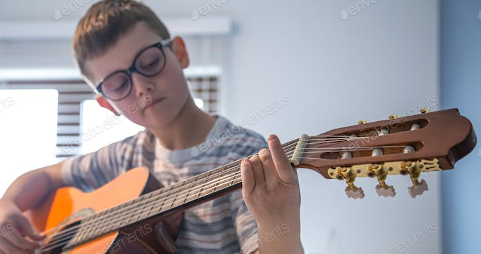Little boy learning to play the classical guitar.