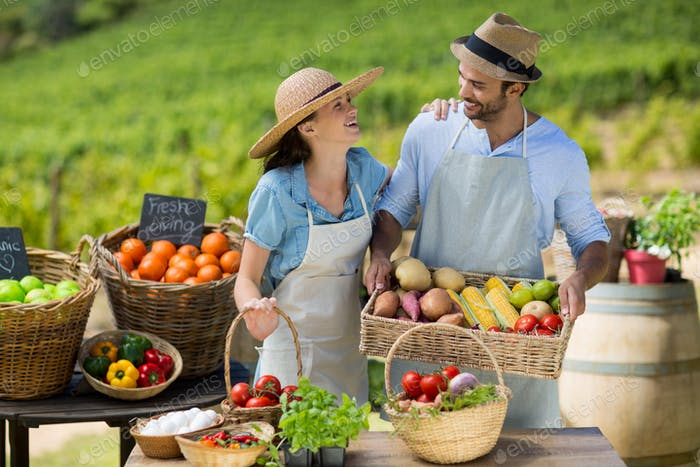 Happy couple standing by fresh fruits and vegetables