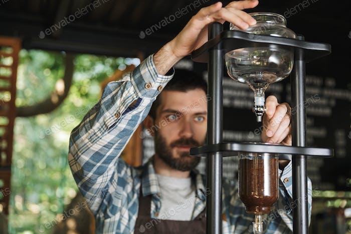 Bild von fokussierten Barista Junge Kaffee machen während der Arbeit im Café