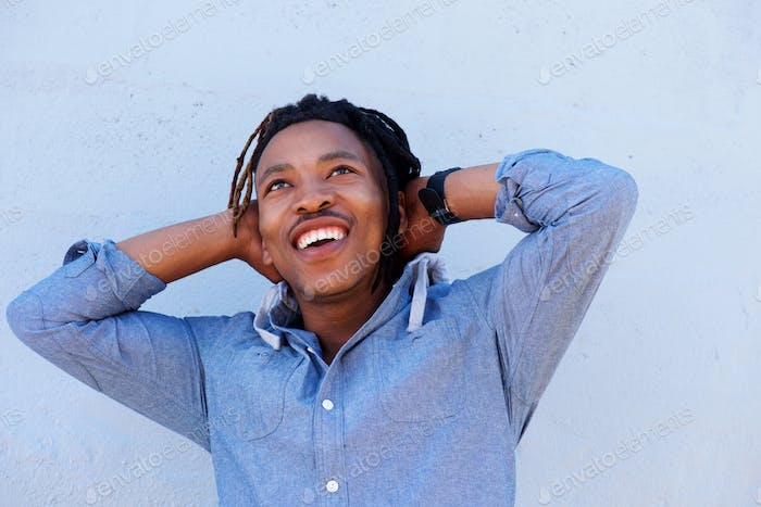 cheerful african man laughing with hands behind head