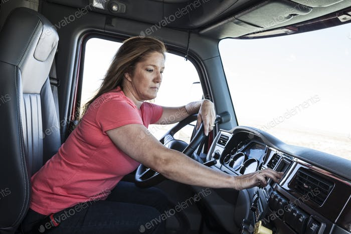 Caucasian woman driver parked and using the GPS mapping device in the cab of a  commercial truck.