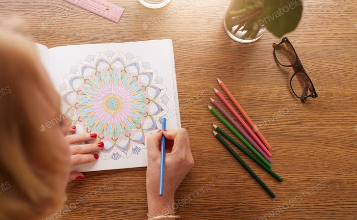 Woman coloring with color pencils for relaxation