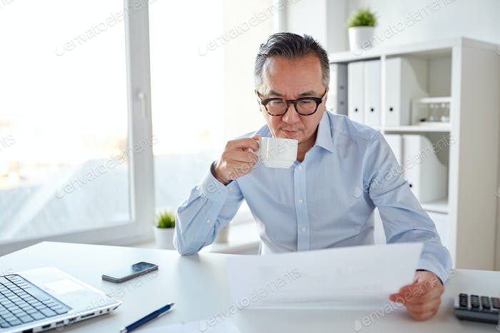 businessman with papers drinking coffee at office