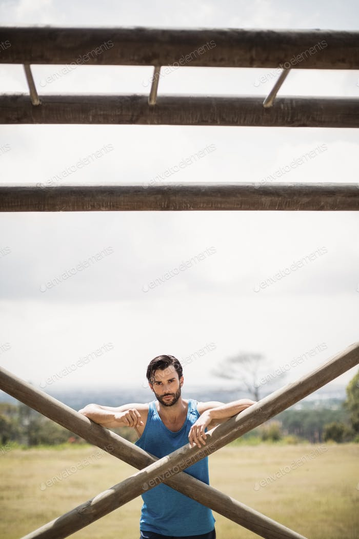 Portrait of fit man leaning on wooden bar during obstacle course