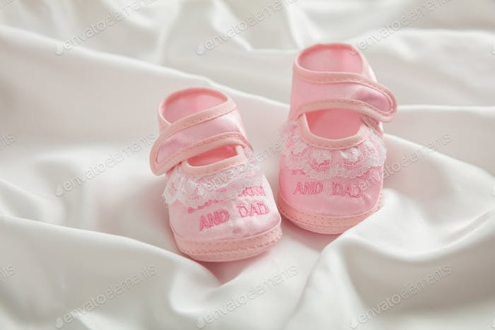 Baby girl shoes  on white satin, copy space
