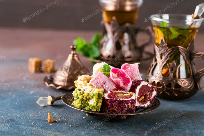 Bowl with various pieces of turkish delight lokum and black tea with mint on a dark background