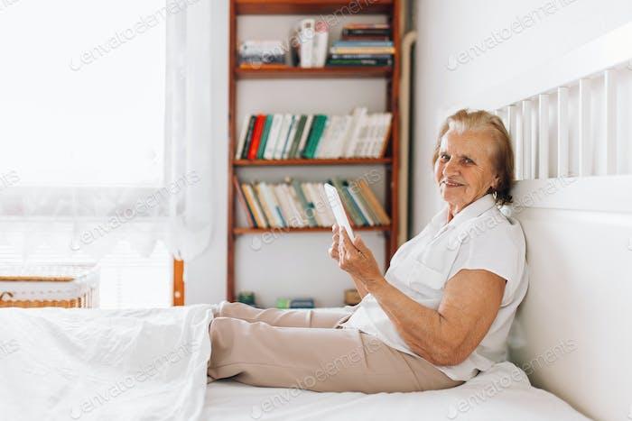 Ältere Frau sitzt bequem auf dem Bett und mit ihrem Tablet