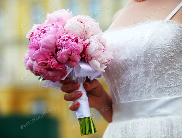 Closeup view of a bride holding bouquet of peonies